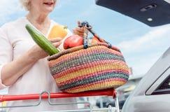 Gladlynt hög kvinna som rymmer en korg full av nya grönsaker arkivfoto