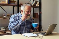 Gladlynt hög man med kakor och koppen kaffe arkivfoton