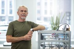 Gladlynt hög man som poserar nära skrivaren 3D Arkivfoton