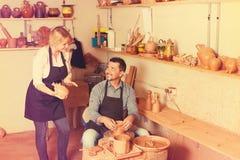 Gladlynt hantverkare som talar till kvinnan i arbetsrum arkivbild