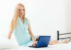 Gladlynt havandeskapkvinna som vaknar med bärbara datorn Arkivfoton
