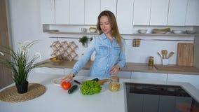 Gladlynt hemmafru som ler med tomaten i händer och förbereder sallad som står i mitt av kök under dag arkivfilmer