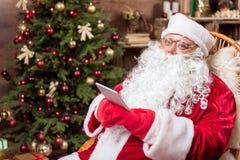 Gladlynt hemmastadd Santa Claus hållande minnestavla Fotografering för Bildbyråer