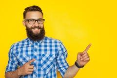 Gladlynt hipster som pekar på sida royaltyfri bild