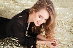 Gladlynt härlig ung kvinna i svart klänning med långt hår Royaltyfri Fotografi