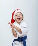 Gladlynt idrottsman nenflicka i en kimono och en beanie Santa Claus Arkivbild