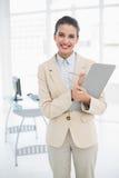 Gladlynt ila den bruna haired affärskvinnan som kontrollerar en rapport arkivfoton