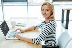 Gladlynt intelligent kvinna som arbetar på bärbara datorn royaltyfri foto