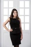 Gladlynt klänning för svart för modemodell som bakom poserar och ler i dörrar för studiovindhemmiljö Royaltyfri Bild