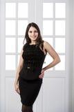 Gladlynt klänning för svart för modemodell som bakom poserar och ler i dörrar för studiovindhemmiljö Royaltyfri Foto