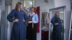 Gladlynt klient som bär den nya sydde klänningen i seminarium arkivfilmer