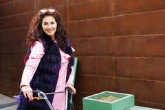 Gladlynt kvinna i en rosa klänning och en purpurfärgad pälsudde som rider en sparkcykel arkivbild