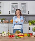 Gladlynt kvinna i köket arkivfoton