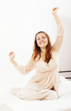 Gladlynt kvinna i nightrobe som hemma vaknar i säng Royaltyfria Bilder