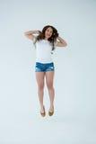 Gladlynt kvinna, i vit t-skjorta och för varma flåsanden att hoppa Arkivfoton