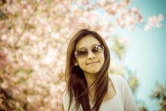 Gladlynt kvinna med det rosa körsbärsröda trädet Arkivfoto