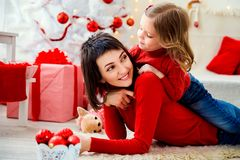 Gladlynt kvinna med dottern i jultid Fotografering för Bildbyråer