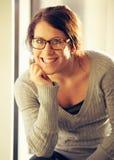 Gladlynt kvinna med glasögon som ser dig Arkivbild