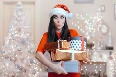 Gladlynt kvinna med många julklappar i dekorerat hem arkivfoton