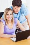 Gladlynt kvinna och henne pojkvän som använder en bärbar dator Arkivbild