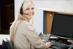 Gladlynt kvinna som använder datoren på mottagandeskrivbordet Arkivbild