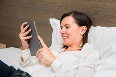 Gladlynt kvinna som använder hennes minnestavla i sovrum Arkivfoto