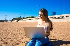 Gladlynt kvinna som använder netbook, medan vila utomhus royaltyfri bild