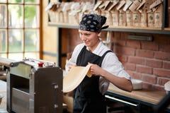 Gladlynt kvinna som arbetar med pastamaskinen royaltyfri fotografi