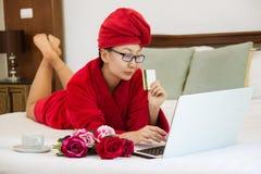 Gladlynt kvinna som direktanslutet shoppar med kreditkort- och bärbar datordatoren på en säng arkivfoton