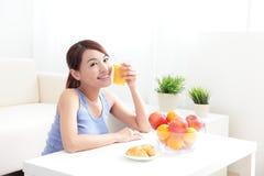 Gladlynt kvinna som dricker en orange fruktsaft Royaltyfria Bilder