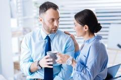 Gladlynt kvinna som erbjuder hennes trötta förvånade kollega per koppen av smakligt te royaltyfria foton