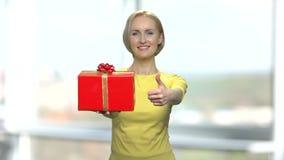 Gladlynt kvinna som ger upp den gåvaasken och tummen lager videofilmer
