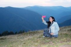 Gladlynt kvinna som gör selfie i bergen Arkivfoto