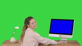 Gladlynt kvinna som i regeringsställning sitter på tabellen med en dator och ser kameran som ler Blue Screen modellskärm stock video