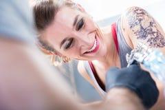 Gladlynt kvinna som ler med förtroende i en modern tatueringstudio royaltyfria bilder