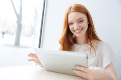 Gladlynt kvinna som ler och använder minnestavlan i kafé Royaltyfria Foton