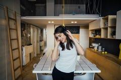 Gladlynt kvinna som lyssnar till musik med stor hörlurar och att sjunga Musikterapi, välgörande övning för lynne mental hälsa arkivfoto