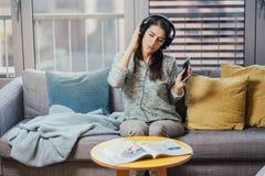 Gladlynt kvinna som lyssnar till musik med stor hörlurar och att sjunga Tycka om att lyssna till musik i fri tid hemma Koppla av  arkivbilder
