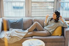 Gladlynt kvinna som lyssnar till musik med stor hörlurar och att sjunga Tycka om att lyssna till musik i fri tid hemma Koppla av  arkivbild