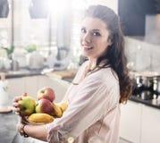 Gladlynt kvinna som rymmer en bunke full av frukt royaltyfri fotografi