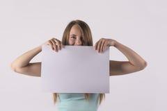Gladlynt kvinna som rymmer ett vitt tomt baner Arkivbild