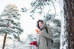 Gladlynt kvinna som smsar på den orange smartphonen under en tur till skogen i vinter Brunettmodell som bär det varma omslaget Royaltyfri Fotografi