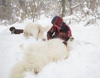 Gladlynt kvinna som spelar med hundkapplöpning i snön royaltyfria bilder