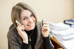 Gladlynt kvinna som talar på de två telefonerna på samma tid Arkivfoton
