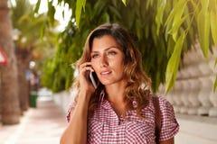 Gladlynt kvinna som utomhus talar till mobiltelefonen Arkivfoton