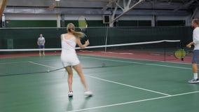 Gladlynt kvinnaanseende mot tennislaget på domstolen stock video