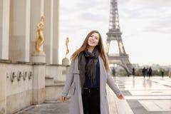 Gladlynt kvinnaanseende på Trocadero den fyrkantiga near förgyllda statyer och Eiffeltorn Arkivbilder