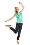 Gladlynt kvinnaanseende på ett ben med lyftta händer Royaltyfria Foton