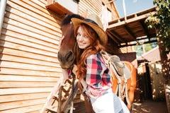 Gladlynt kvinnacowgirl som står och kramar hennes häst på lantgård arkivfoton