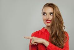 Gladlynt kvinnamodellstående Nätt flicka som ler och pekar på vit bakgrund royaltyfri foto